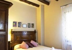 Dormitorio con cama de matrimonio y cojines rosas