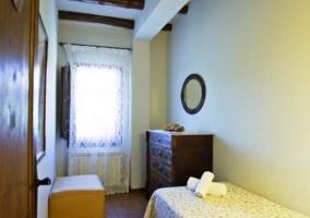 Dormitorio con una cama individual y vigas de madera
