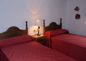 Dos camas y mesa de noche de madera