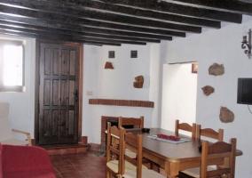 Mesa de madera, sofá rojo y cocina