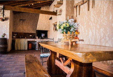 Vistas del porche con barbacoa y mesas de madera