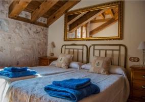 Dormitorio con camas individuales y techos abuhardillados