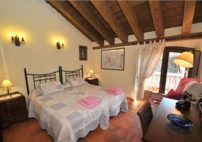 Dormitorio con camas individuales y balcon