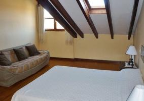 Dormitorio con cama de matrimonio abuhardillado
