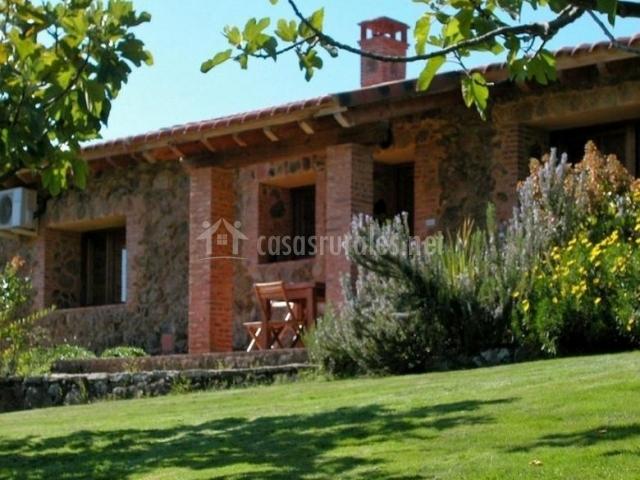 Vistas de la fachada con terraza y jardín