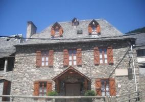 Acceso principal a la casa con muros de piedra