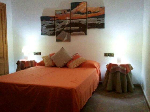 Dormitorio de matrimonio con colcha naranja