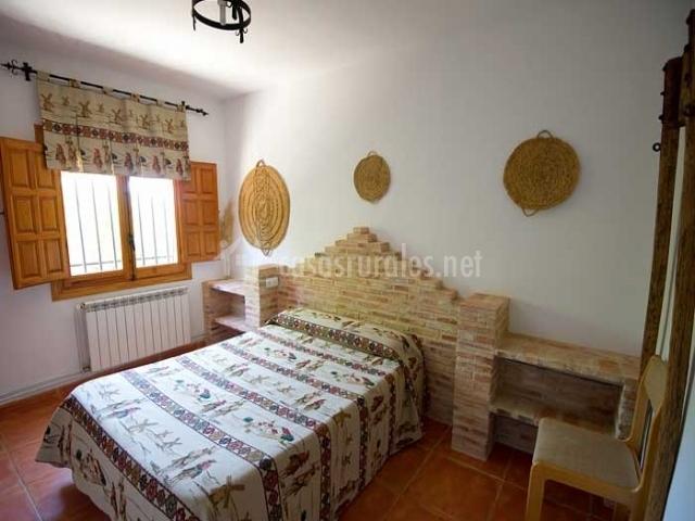 Dormitorio con cabecero de ladrillo