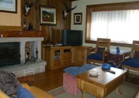 Sala de estar con chimenea y una mesa de madera auxiliar