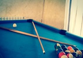 Mesa de billar con palos y bolas