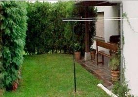Vista del jardín y porche de la casa rural con tendedero