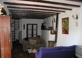 Salón con cocina al fondo y entrada a la casa