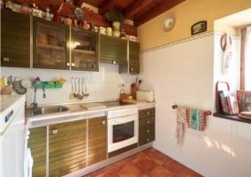 Cocina de azulejos blanco y muebles madera
