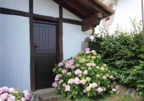 Puerta de exterior en jardín con flores