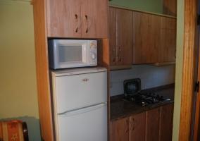 Cocina con muebles, microondas y nevera