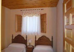 Dormitorio doble con dos camas y cabeceros de madera