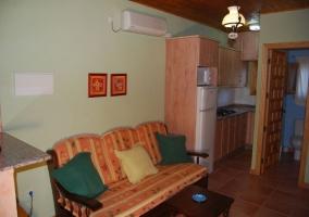 Salón con sillón, cocina y acceso al aseo