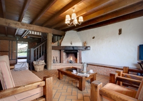 Salón con chimenea, sillones y comedor al fondo
