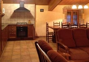 Salón comedor con sillones y mesa y cocina