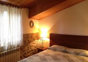 Dormitorio con cama de matrimonio y pared con piedras