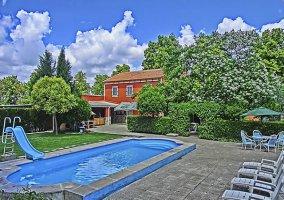 Acceso a la piscina con la casa al fondo