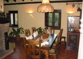 Salón comedor con mesa alargada junto a la chimenea
