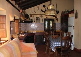 Mesa de madera del comedor junto a la chimenea y la cocina