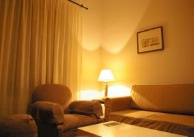 Salón con sillones y televisor sobre mueble blanco