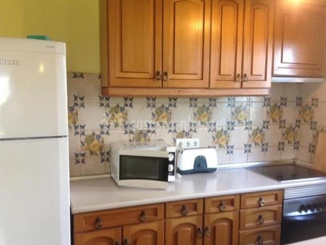 Cocina con armarios de madera y azulejos