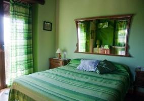 Dormitorio en tonos verdes y espejo pintado
