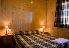 El dormitorio, con madera y mesitas de noche