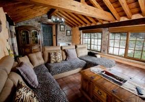 Salón con sillones, televisor, chimenea y techo abuhardillado