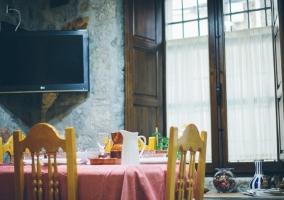 Mesa de comedor con la tele al fondo