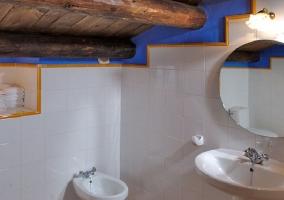 Baño con lavabo y techo de madera