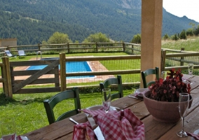 Mesa de comedor en la terraza con piscina al fondo