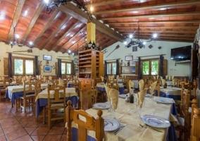 Zona restaurante con vigas de madera y televisión