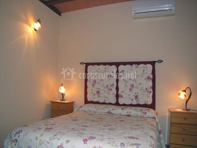 Cama de matrimonio en habitación con aire acondicionado