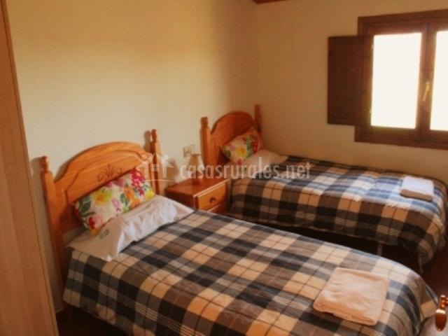 Dormitorio con dos camas individuales y ventana al lado