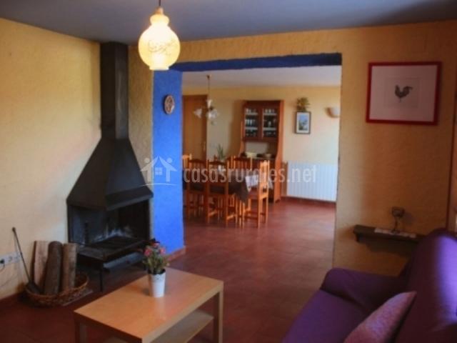 Salón con chimenea y mesa baja y sillón delante