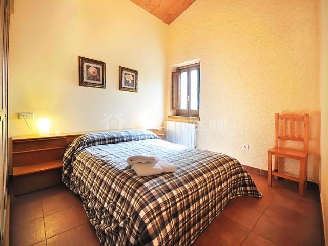 Dormitorio de matrimonio con silla junto a la cama