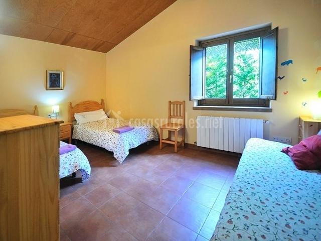 Dormitorio doble con camas individuales y aodornos en la pared