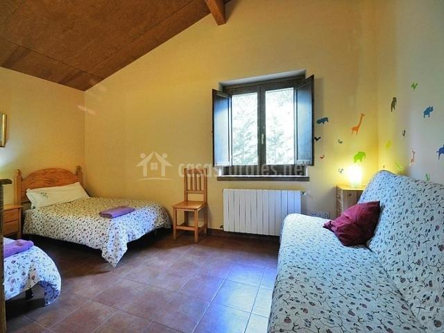 Dormitorio doble con sillón frente a las dos camas