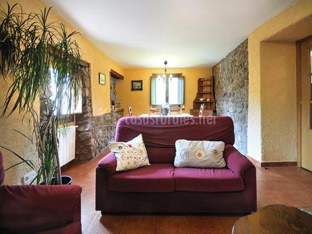 Salón comedor con sillón rojo y mesa de comedor detrás
