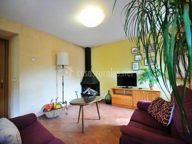 Salón con chimenea en la esquina y mueble con el televisor