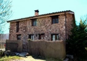 Fachada del alojamiento y entrada con valla