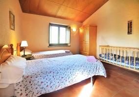 Dormitorio doble con techo abuhardillado y cuna
