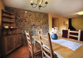 Mesa del comedor junto a alacena y chimenea en el salón