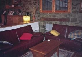 Salón con sofás de cuero y muros de piedra