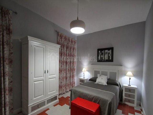 Dormitorio de matrimonio en tonos grises y rojo