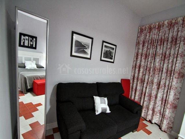 Dormitorio en grises y rojo con sofá